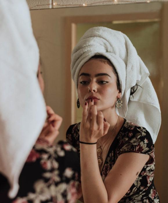 Chica con toalla en la cabeza, frente al espejo arreglándose, poniéndose bálsamo en los labios