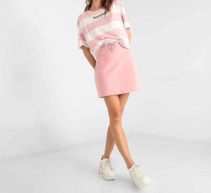 Chica usando falda y playera de marca Superdry