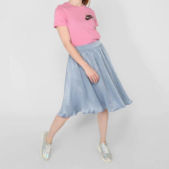 Chica usando playera marca Nike color rosa y falda aterciopelada color azul bebé