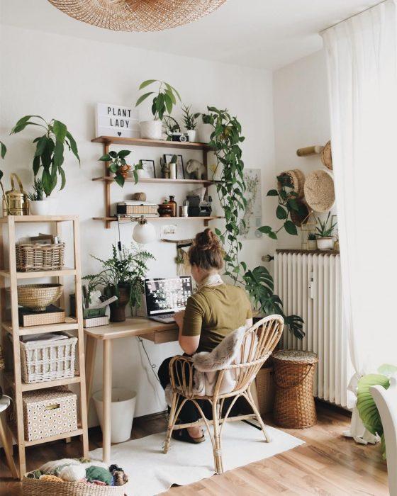 Chica en la computadora, rodeada de plantas