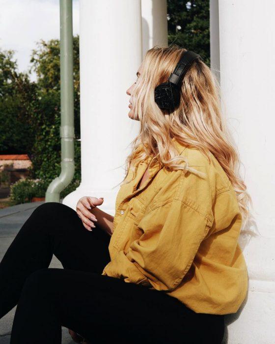 Chica de chamarra amarilla escuchando música con audífonos