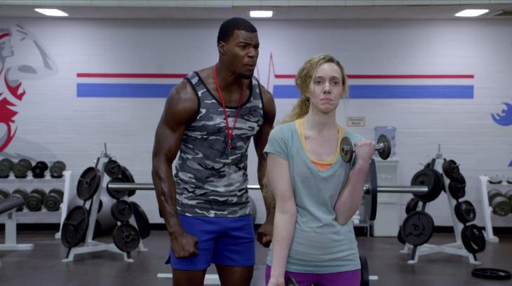 Entrenador gritándole a una chica que hace pesas en el gimnasio