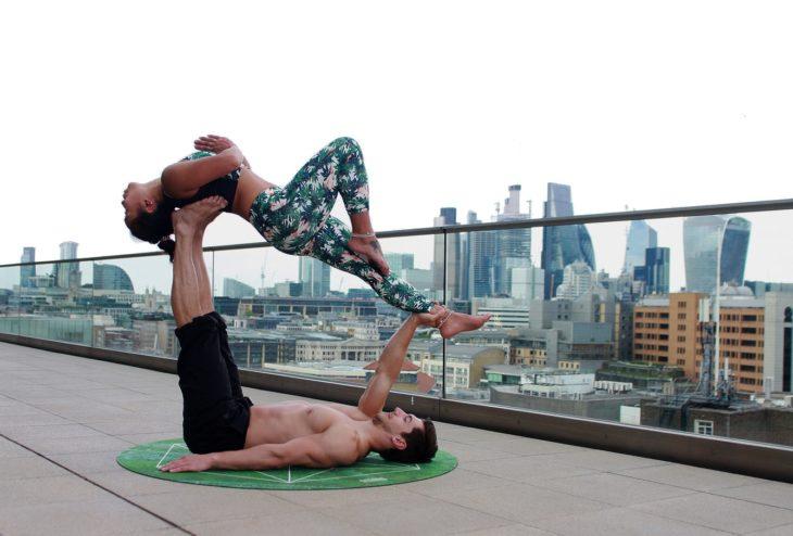 pareja haciendo yoga en una terraza