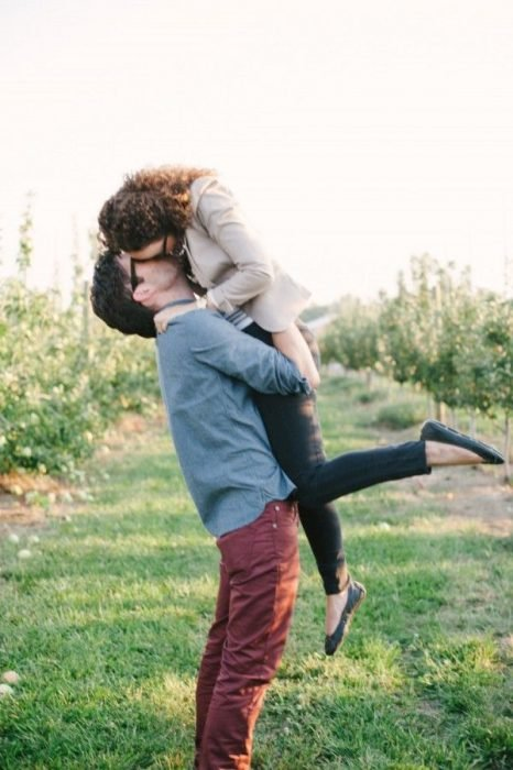 pareja de enamorados en medio del campo besándose mientras él la carga