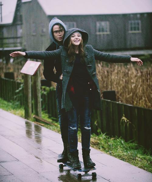 hombre enseñando a una mujer a usar una patineta mientras van por la calle