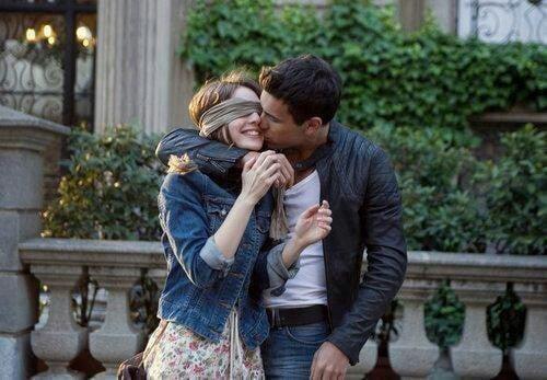 hombre y mujer afuera de una casa mientras el el besa en la mejilla a la chica