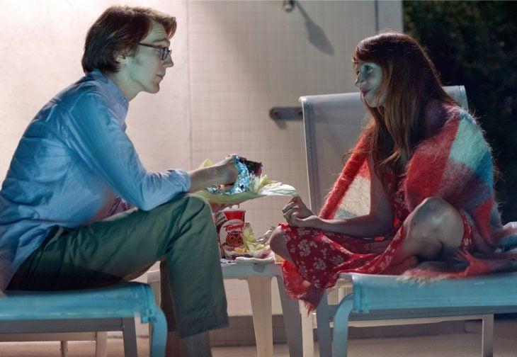 hombre y mujer platicando y comiendo papas y hamburguesas