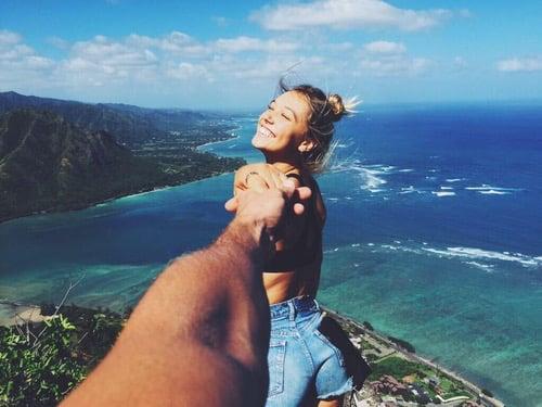 mano de un hombre sosteniendo a una mujer mientras observan el mar