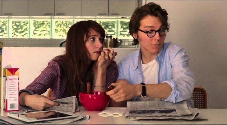 pareja de novios sentados en la mesa mientras el come cereal y lee el periódico y ella le toma la mano