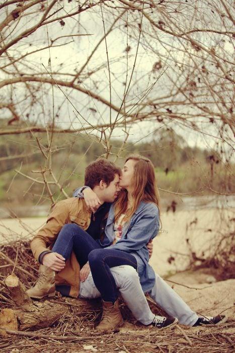 mujer sentada en las piernas de un hombre mientras ella le besa la frente