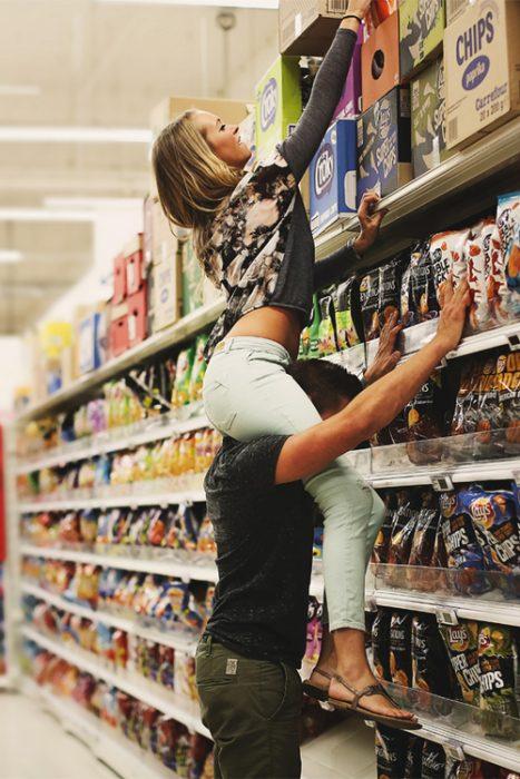 hombre sosteniendo en hombros a una mujer para tomar una caja de un estante