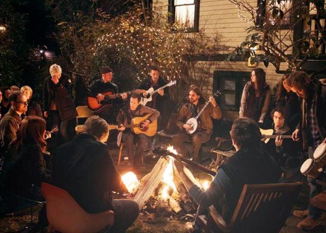 persone attorno a un fuoco che suonano la chitarra e cantano