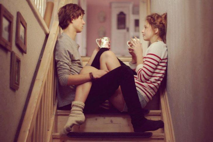 Novios platicando en una escalera mientras toman café