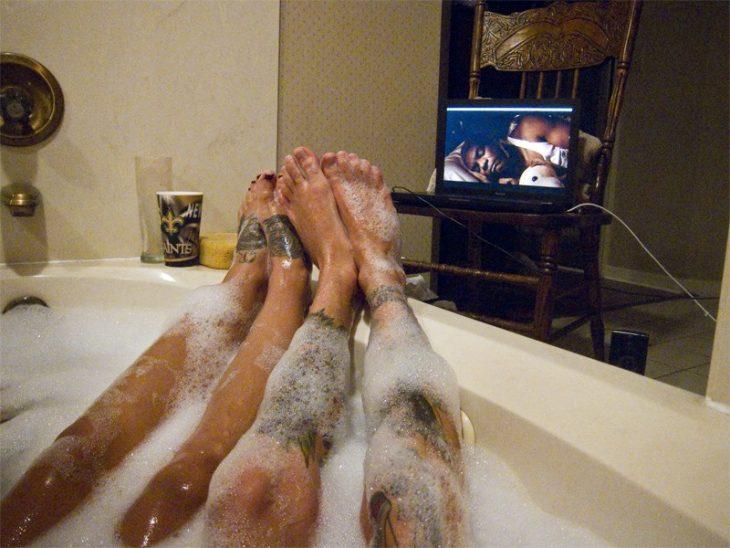 Piernas de pareja en una bañera viendo tele