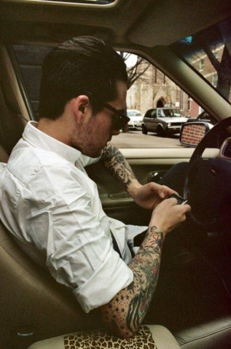 Hombre con tatuajes enviando mensaje de texto por celular
