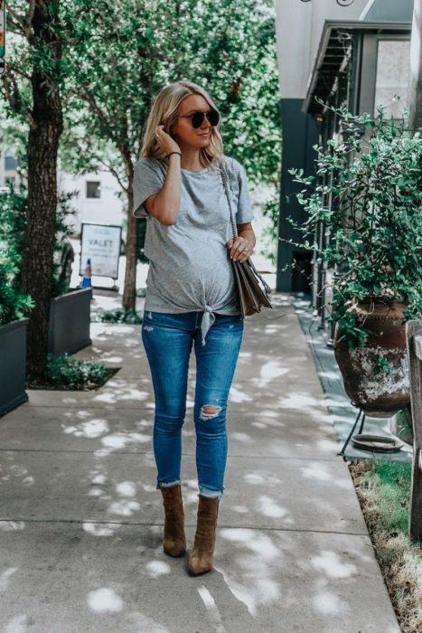 Mujer embarazada con jeans y blusa gris