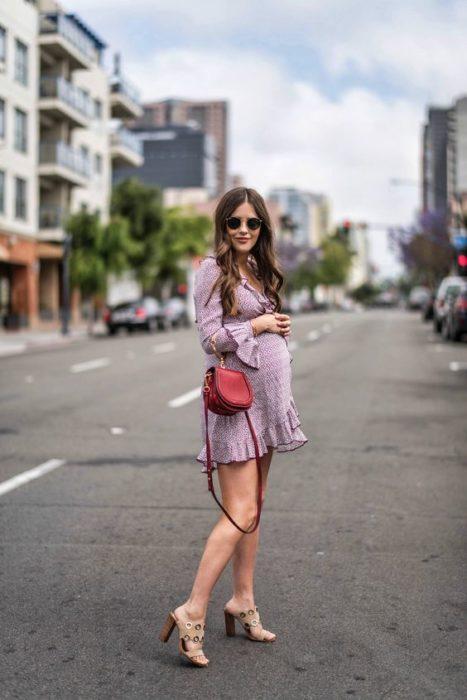 Chica embarazada con vestido morado y bolsa café