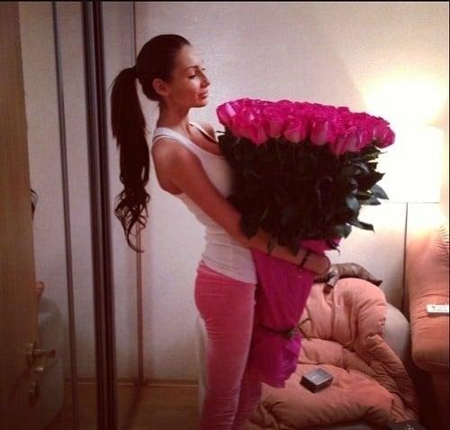 mujer vestida de rosa y blanco parada en medio de una habitación cargando un ramo de rosas grande