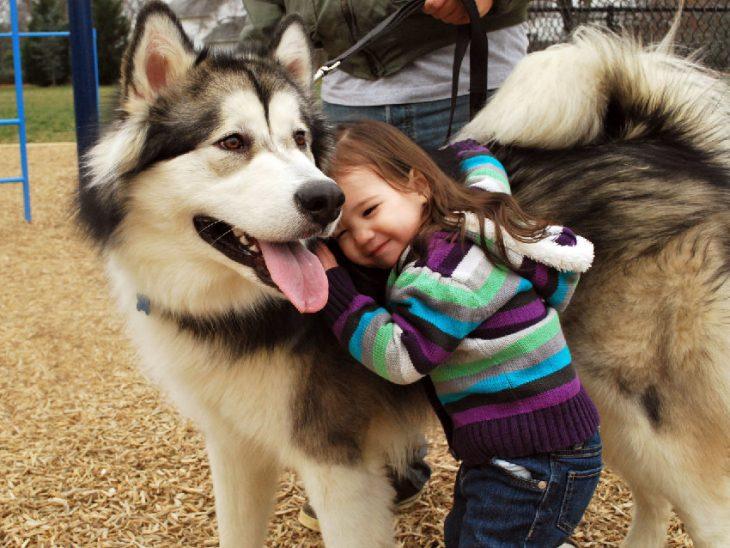 Una niña de pie recargada a un costado de su perro