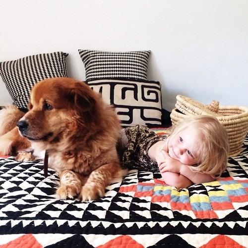 Una niña recostada en la cama con su perro