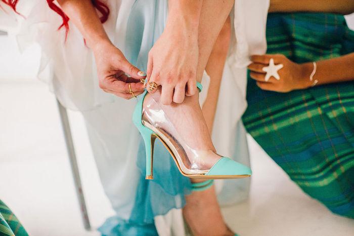 zapatos de color azul con partes transparentes siendo calzados por una mujer