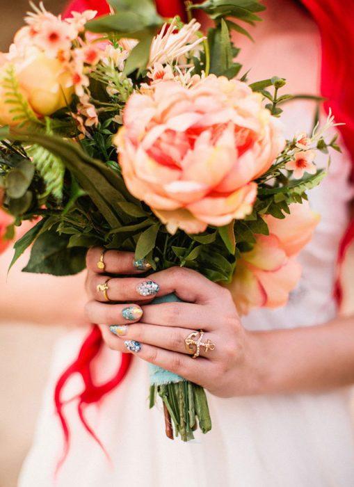 ramo de rosas sostenido por las manos de una mujer con uñas postizas