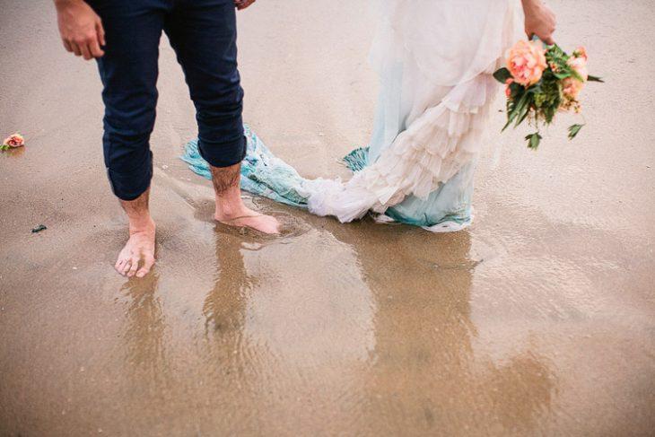 pies de unos novios parados en la playa