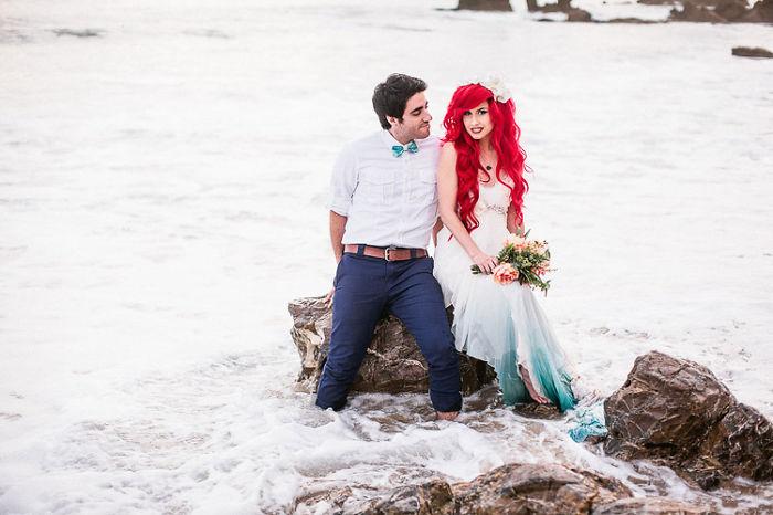 novios sentados en una roca que esta en el mar