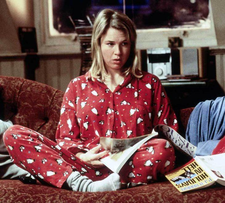 chica sentada en el sofá con pijama roja rodeada de revistas