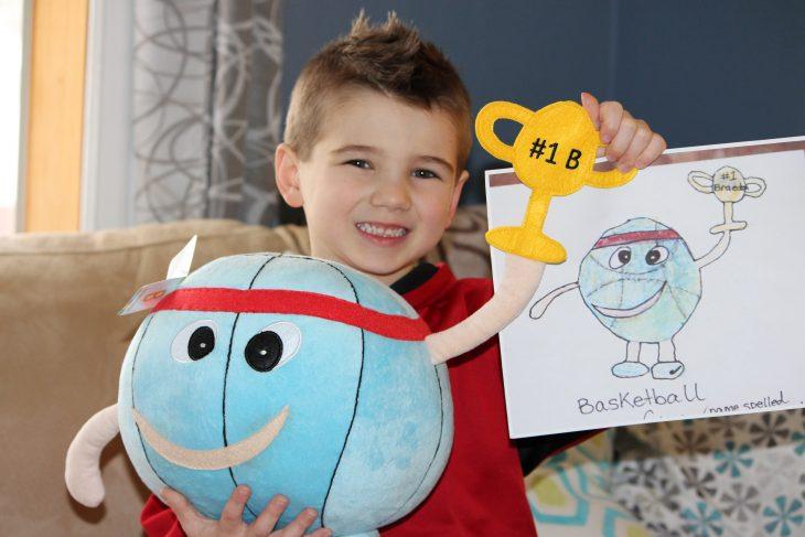 Niño con su dibujo y su peluche de un balón de basketball