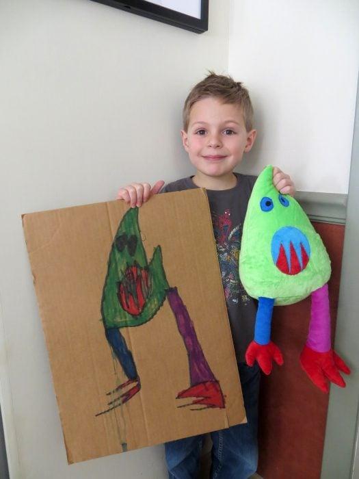 Niño con su dibujo y peluche de budsies