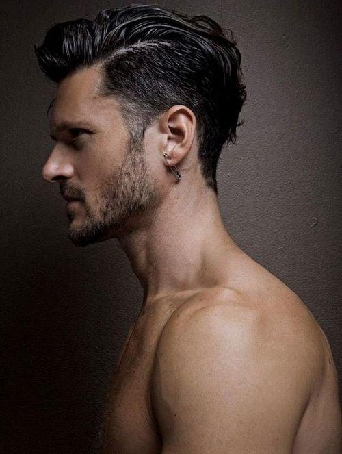 hombre de perfil con barba y cabello corto y un seguro en la oreja