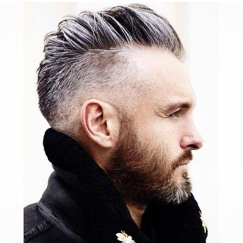 hombre con barba y cabello de color platinado usando un saco negro y posando de perfil