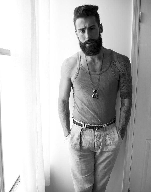 hombre de barba grande usando playera de tirantes con collares en el cuello y múltiples tatuajes en el brazo