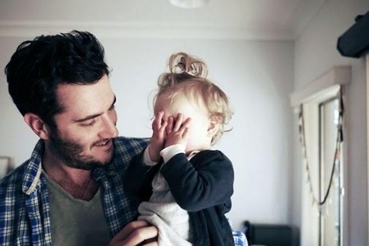Niña pequeña tapándose la cara mientras su papá le habla