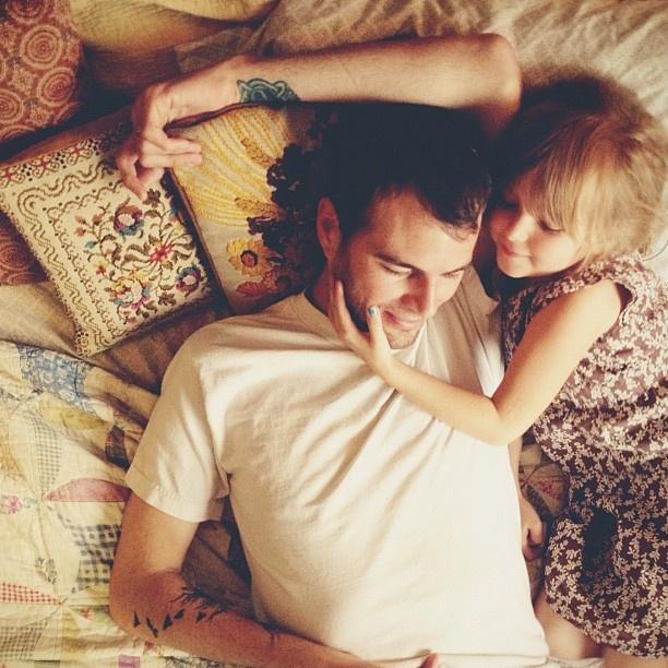 Papá e hija acostados en la cama platicando