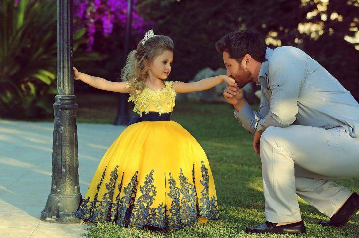 niña vestida de princesa y su papá besandole la mano