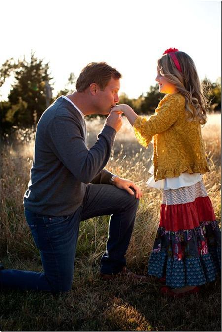 Padre besando la mano de su pequeña hija al atardecer