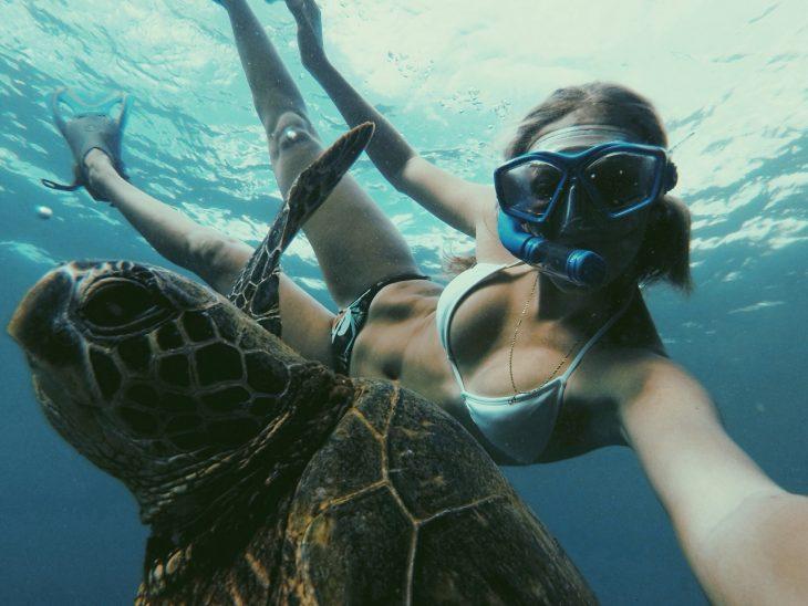 Chica practicando snorkeling con una tortuga marina