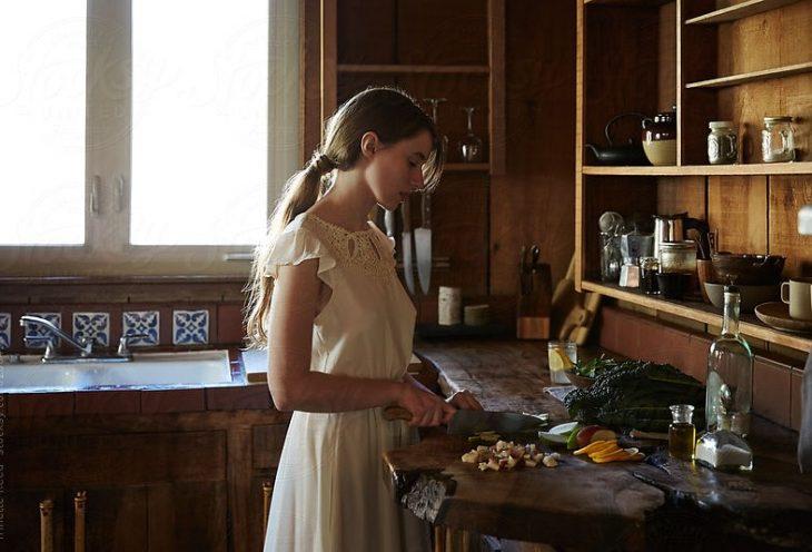 Mujer con vestido blanco cocinando en una cocina rustica