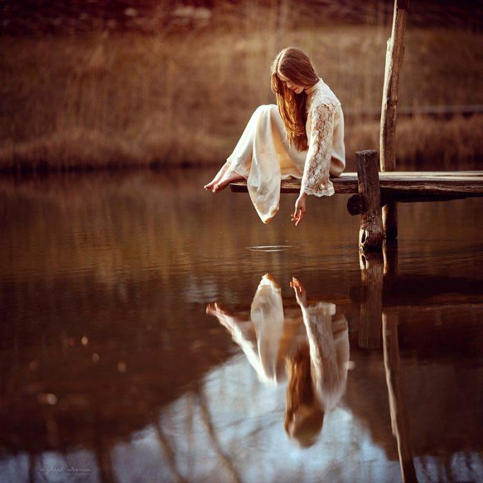 Mujer en el muelle de un río con su reflejo en el agua