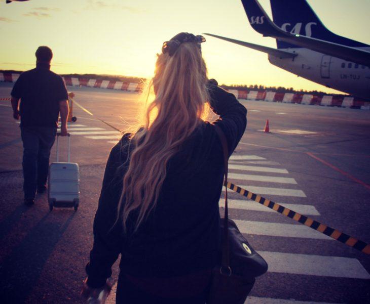 mujer a punto de abordar un avión con la puesta de sol