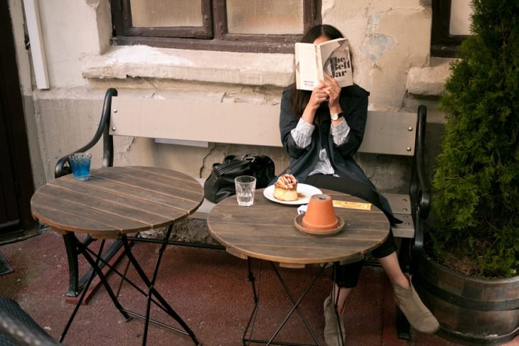 Mujer leyendo en una banca mientras disfruta de un flan y un vaso de agua