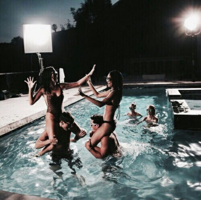 jóvenes jugando en una piscina