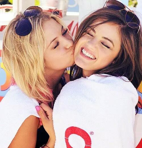 amiga abrazando a la otra y dándole un beso en la mejilla