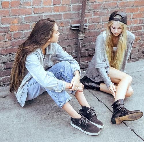 amigas sentadas en la calle conversando