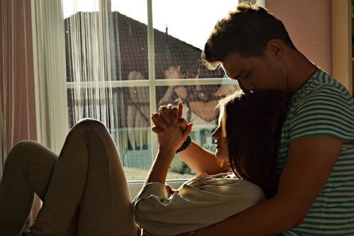 pareja de novios platicando frente a una ventana