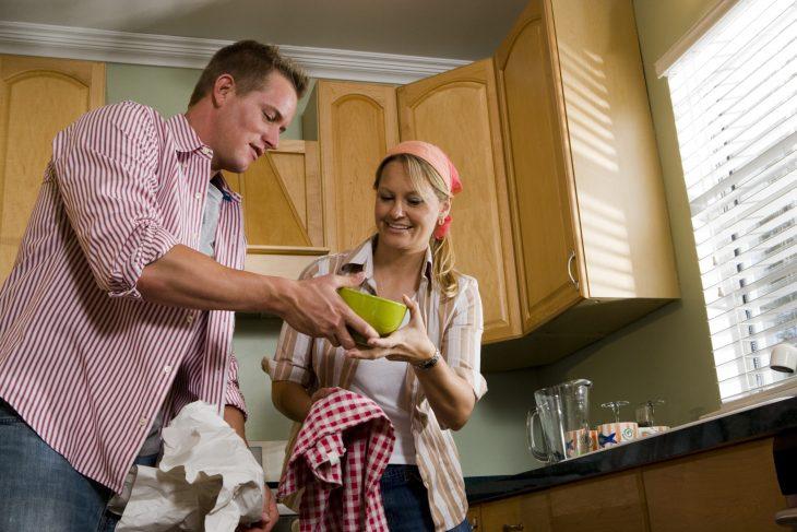 pareja de adultos limpiando la cocina