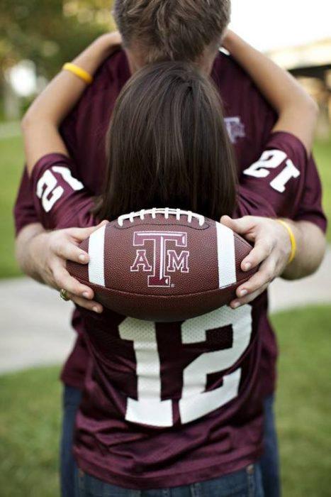 novios abrazados sosteniendo un balón de fútbol americano