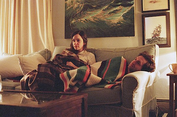 novios recostados en el sofá viendo la television